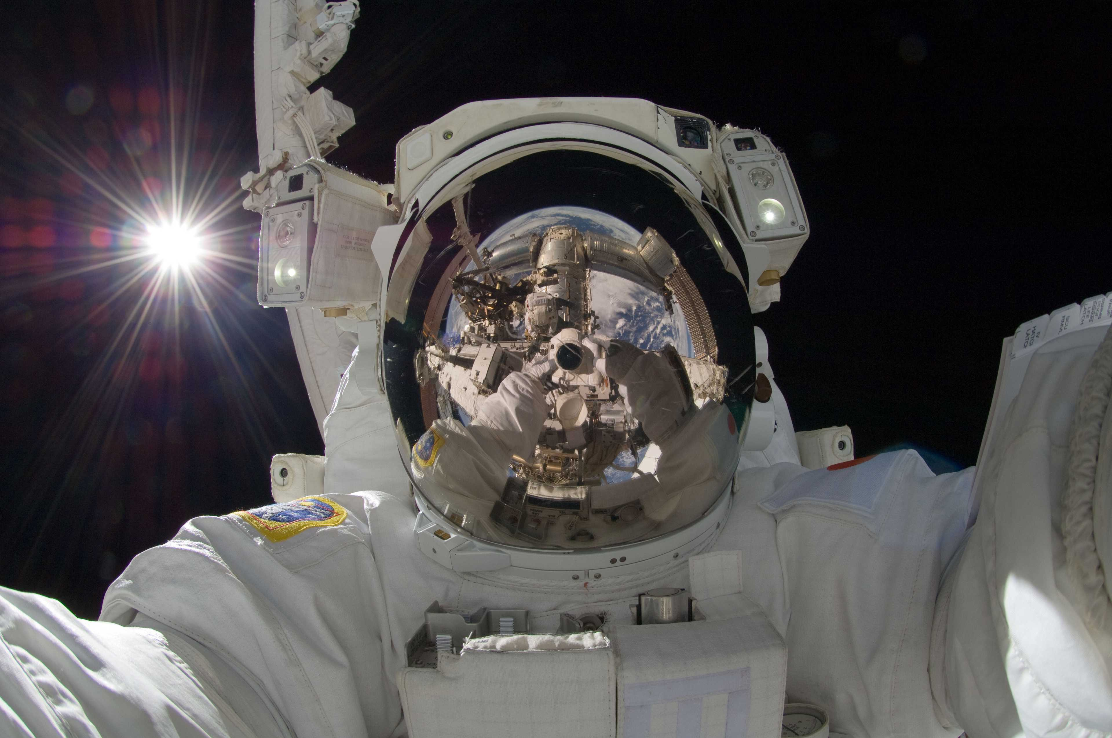 astronaut Aki Hoshide taking a self portrait in a spacesuit with the sun behind him and the camera, ISS and Earth visible in his visor