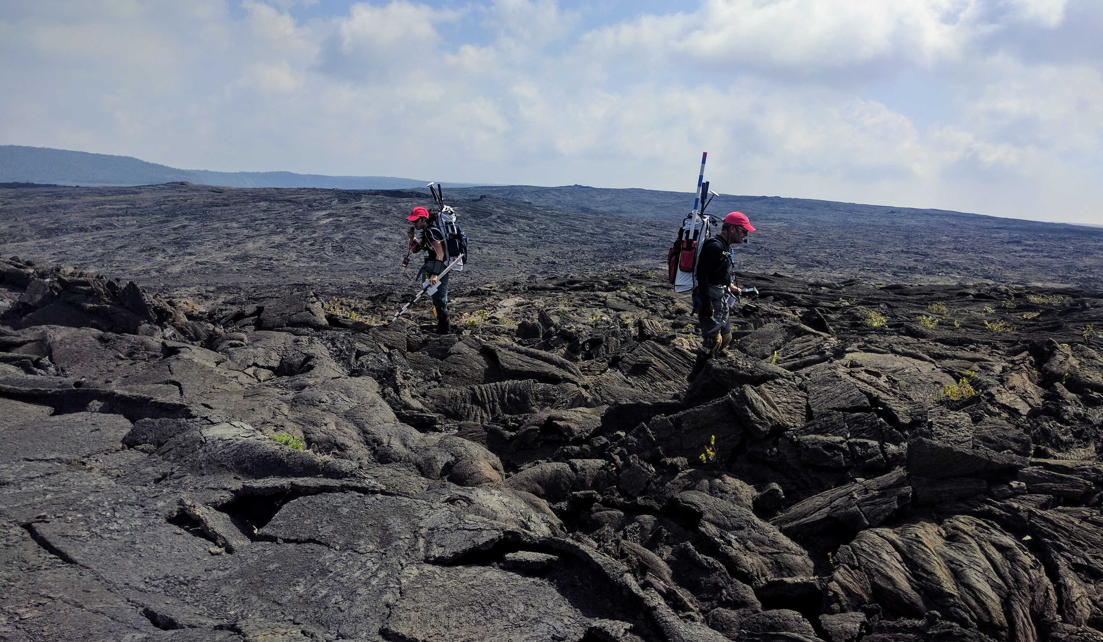 two simulated astronauts walking around on mountainous, basalt-y terrain. they have backpacks with communication equipment and appear to be surveying the surrounding area for potential sample locations