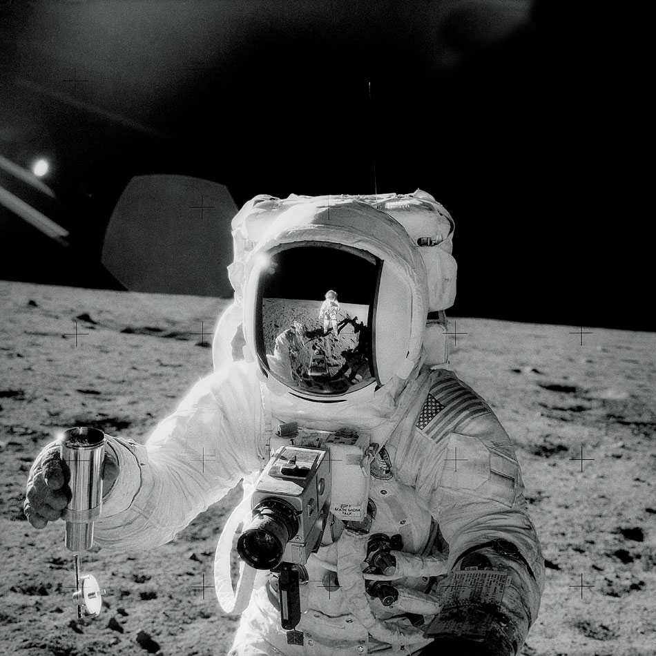 a black and white photo of astronaut Alan Bean collecting lunar soil.