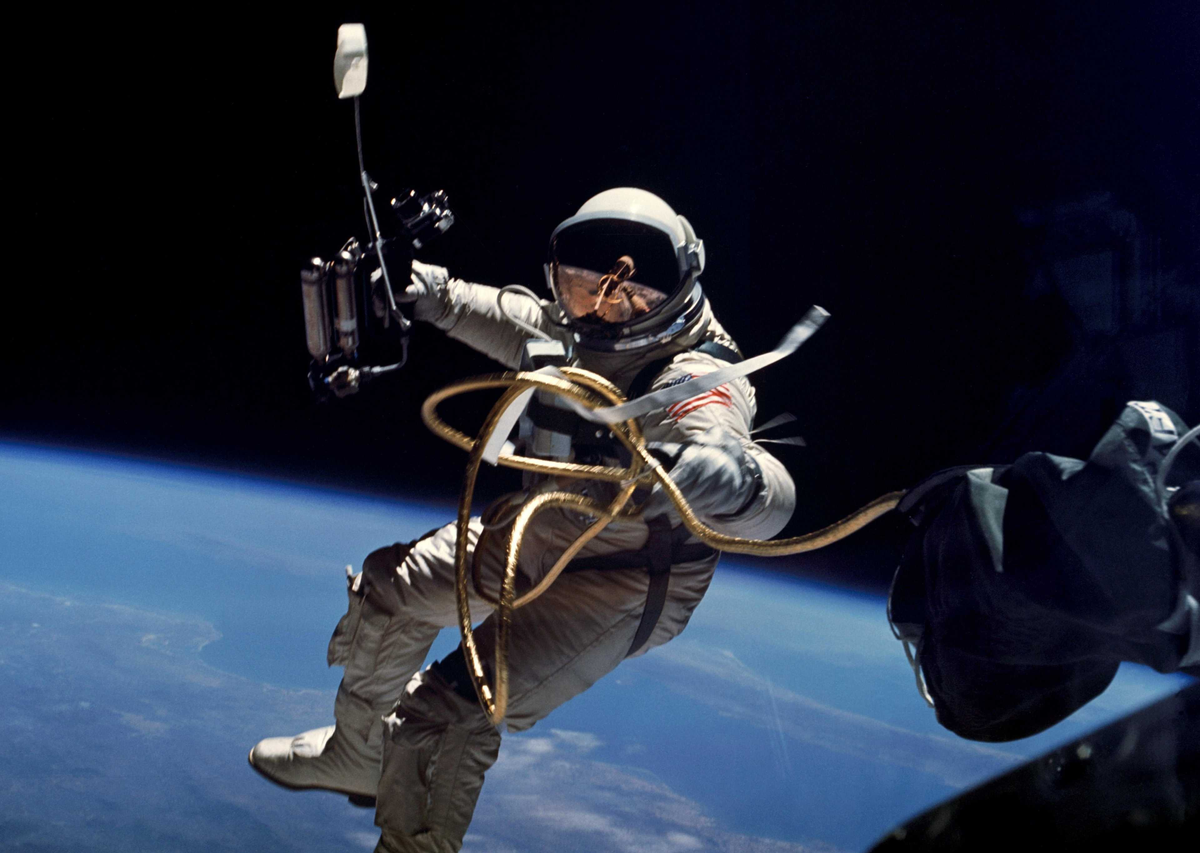astronaut Edward White in space with the earth below him. a gold tether keeps him attached to Gemini 4.