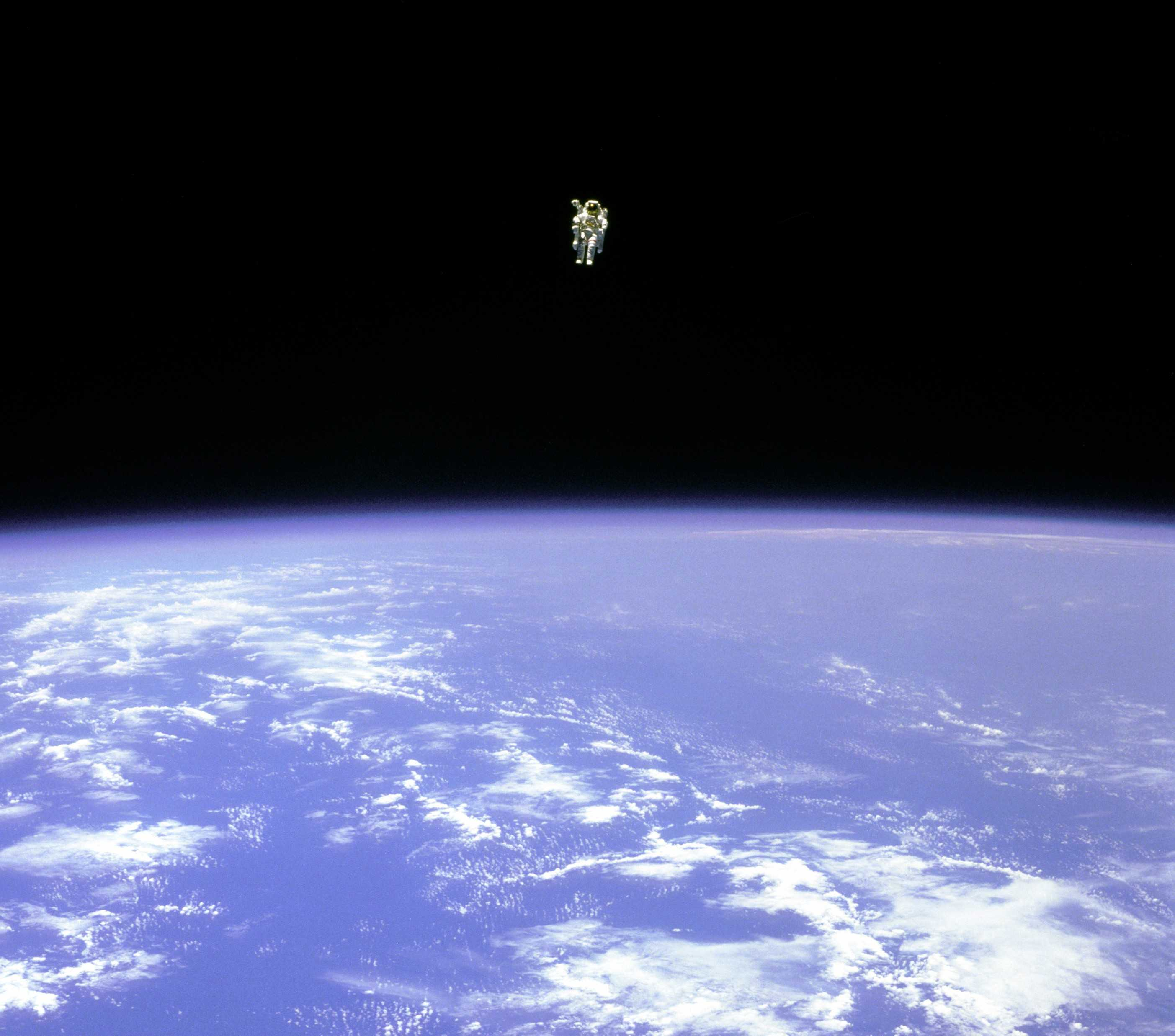 astronaut Bruce McCandless II free floating in a spacesuit over the earth