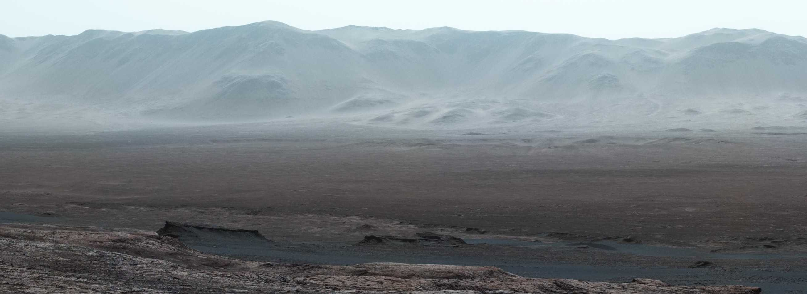 a panorama on mars. the sky is tinted blue, a drop into a valley is in the foreground, with the rising edge of a crater in the background